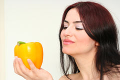 Woman and yellow peper. Oriental pretty girl with yellow peper in a hand Royalty Free Stock Photo