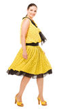Woman in yellow polka-dot dress retro. Woman demonstrates the casual clothes on white background Royalty Free Stock Image