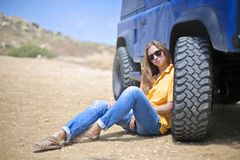 Woman in Yellow Polo Shirt Sitting on Ground Leaning on Blue Vehicle at Daytime Royalty Free Stock Images