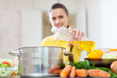 Woman in yellow pours oil from bottle. Into the pan. Focus on bottle Stock Images