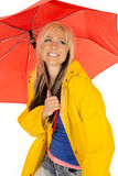 Woman in yellow rain coat under red umbrella happy royalty free stock photos