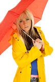 Woman in yellow rain coat under red umbrella serious Royalty Free Stock Images