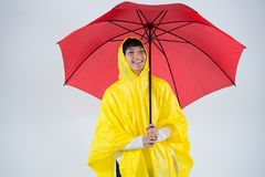 Woman in yellow raincoat holding an umbrella. Smiling woman in yellow raincoat holding an umbrella Royalty Free Stock Photography