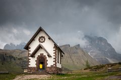 Woman in a yellow raincoat infront of chapel at Rolle Pass, Ital. A woman in a yellow raincoat standing infront of the Chapel at Rolle Pass, one of the oldest Stock Photos