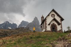 Woman in a yellow raincoat infront of chapel at Rolle Pass, Ital. A woman in a yellow raincoat standing infront of the Chapel at Rolle Pass, one of the oldest Royalty Free Stock Photo