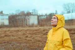 Woman in yellow raincoat looking up at rainy clouds. While the raindrops are falling on her face royalty free stock image