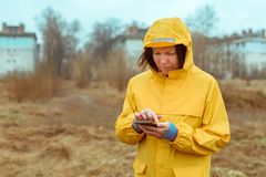 Woman in yellow raincoat texting on mobile phone outdoors. On rainy day stock image