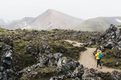 Woman in yellow raincoat walking through the lava field towards foggy mountains in Landmannalaugar national park, Iceland.  royalty free stock photos