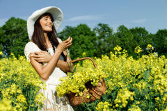 Woman in the yellow rape field Royalty Free Stock Image