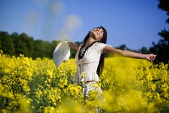 Woman in the yellow rape field Stock Images