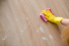 Woman in yellow rubber gloves cleaning table Royalty Free Stock Image