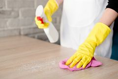 Woman in yellow rubber gloves cleaning table Royalty Free Stock Photo