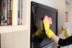 Woman in yellow rubber gloves cleaning tv royalty free stock photos
