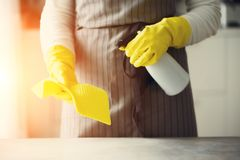 Woman in yellow rubber protective gloves wiping dust and dirty. Cleaning concept, banner, copy space.  Royalty Free Stock Photography