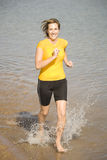 Woman in yellow running in water. Woman wearing yellow running and splashing in the water Royalty Free Stock Image