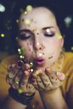Woman in Yellow Shirt Blowing a Gold Star Glitter Royalty Free Stock Photo