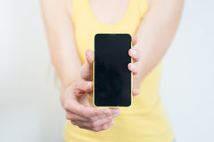 Woman in a yellow shirt holding a mobile phone Royalty Free Stock Image