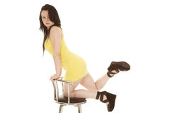 Woman yellow short dress kneeling on chair Stock Image