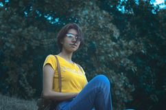 Woman in Yellow Short-sleeved Top and Blue Denim Jeans royalty free stock image