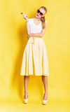 Woman in yellow skirt with lollipop Stock Images