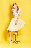 Woman in yellow skirt with lollipop sitting on chair. On yellow background Stock Image