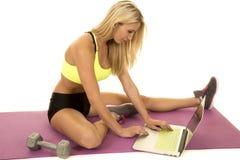 Woman yellow sports bra sit by laptop side Royalty Free Stock Image