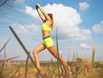 Woman in Yellow Sports Bra Stretching Near Green Grass Field Royalty Free Stock Images