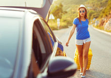 Woman with a yellow suitcase goes to a car parked on the roadsid Stock Images