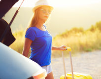 Woman with a yellow suitcase standing near the trunk of a car pa Stock Photos