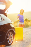 Woman with a yellow suitcase standing near the trunk of a car pa Royalty Free Stock Photo