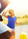 Woman with a yellow suitcase standing near the trunk of a car pa Royalty Free Stock Photos