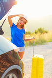 Woman with a yellow suitcase standing near the trunk of a car pa Royalty Free Stock Photography
