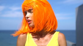 Woman in yellow swimsuit and orange wig stock video