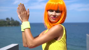 Woman in yellow swimsuit and orange wig stock video footage