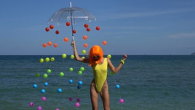 Woman in yellow swimsuit and orange wig stock footage