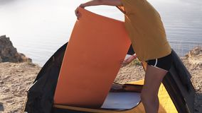 A woman in yellow T shirt setting up or removing mattress from a camping tent. Footage from a top of the cliff. Camping
