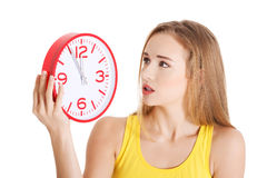 Woman in yellow top holding a clock. Stock Photo