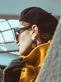 Woman in Yellow Trench Coat, Black Leather Gloves, Black Sunglasses and Black Hat Royalty Free Stock Photography