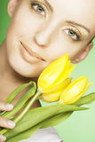 Woman with yellow tulips over green background Stock Photography