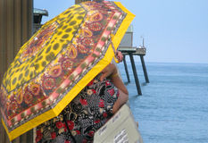 Woman with Yellow Umbrella. A woman leaning on a pier looking out to sea on a sunny day with a colorful yellow umbrella Stock Image