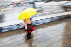 In the rain. Woman with a yellow umbrella walking in the rainy city, shown in motion blur Stock Photography