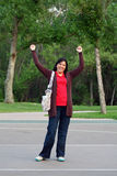 Woman yells Hooray!. A tall, pretty dark-haired woman stands with hands raised in the air. She is excited about something and has a huge smile. She is wearing a Stock Photography
