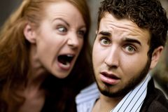 Woman Yells at Man. Young woman yells at man with beard Stock Image