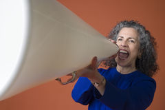 Woman yells into a megaphone. Woman yelling with a megaphone on an orange background Stock Images