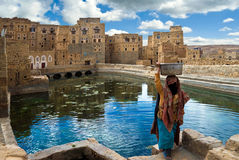 Woman in Yemen. An unidentified woman, dressed in traditional clothes, uses a public fountain basin in order to fetch water home on May 5, 2007 in Thula, Yemen Stock Images
