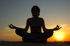 Woman  yoga. Silhouette of sitting woman by making yoga Royalty Free Stock Photo