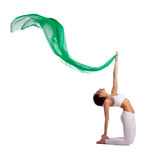 Woman in yoga asana with green fabric in air Stock Photo