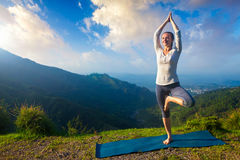 Woman in  yoga asana Vrikshasana tree pose in mountains outdoors Royalty Free Stock Images