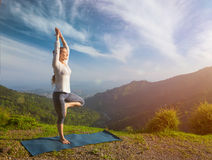 Woman in  yoga asana Vrikshasana tree pose in mountains outdoors Royalty Free Stock Image
