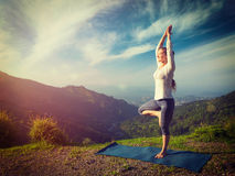 Woman in  yoga asana Vrikshasana tree pose in mountains outdoors Stock Images